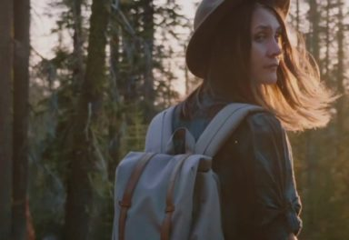 Woman hiking with hat and backpack