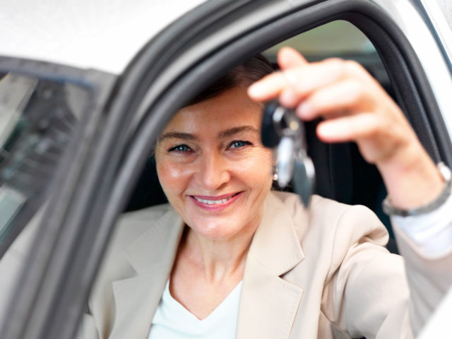 Woman holding keys after vehicle purchase