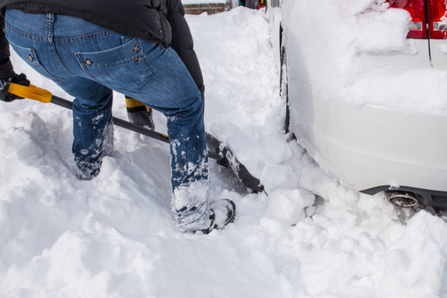 Shovelling snow from under car