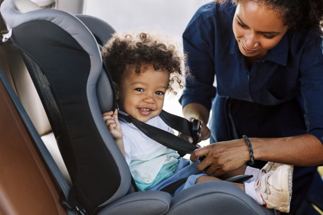 Young child sitting in a front facing car seat in a vehicle