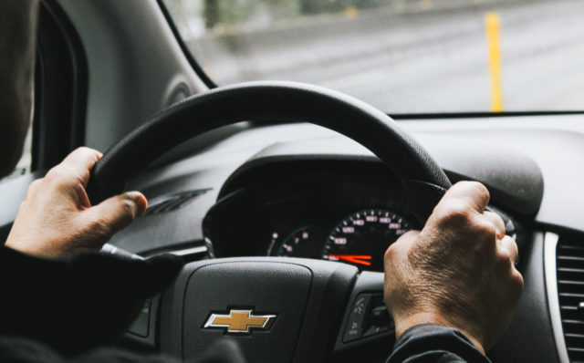 Man in car with hand on steering wheel