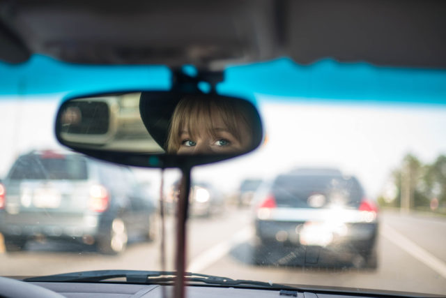 Woman looking in rearview mirror while driving