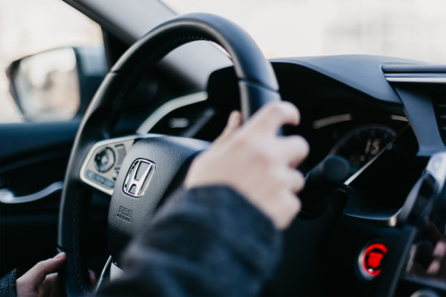 Person with hands on a car steering wheel